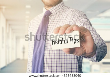 businessman in office showing card with text: Helpful Tips - stock photo