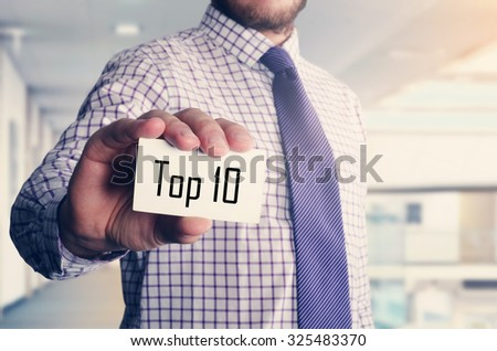 businessman in office showing card with text: Top 10 - stock photo