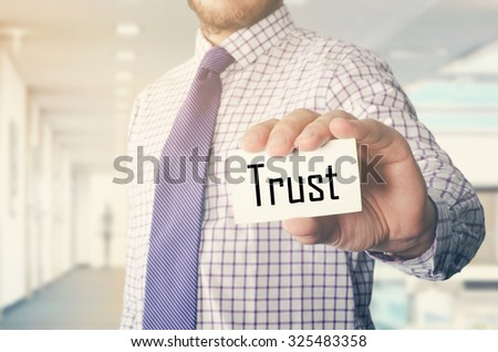 businessman in office showing card with text: Trust - stock photo
