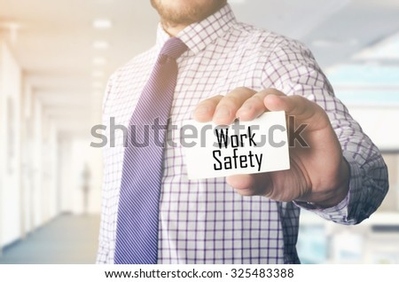 businessman in office showing card with text: Work Safety  - stock photo
