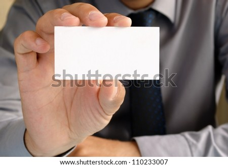 Businessman in office shows the business card in his hand