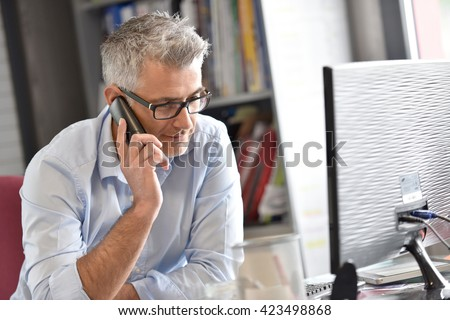 Businessman in office talking on phone  - stock photo
