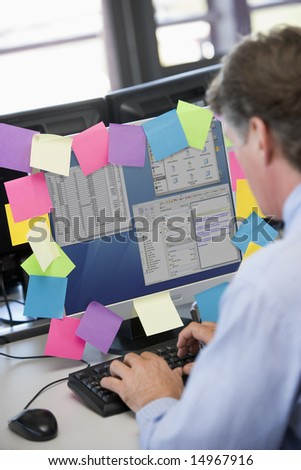 Businessman in office typing at computer with notes on it - stock photo
