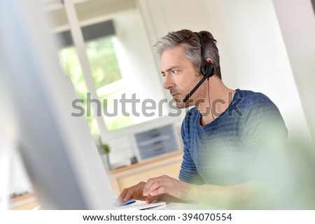 Businessman in office using phone headset