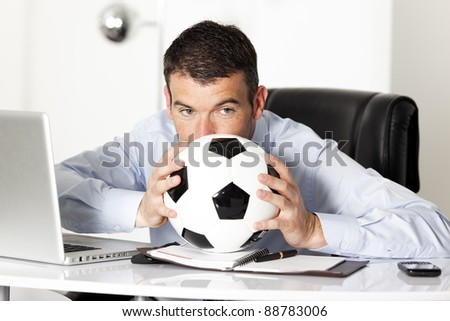 businessman in office with computer and ball - stock photo