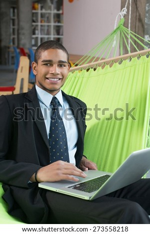 Businessman in office with notebook smile after online deal - stock photo