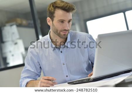 Businessman in office working on laptop  - stock photo