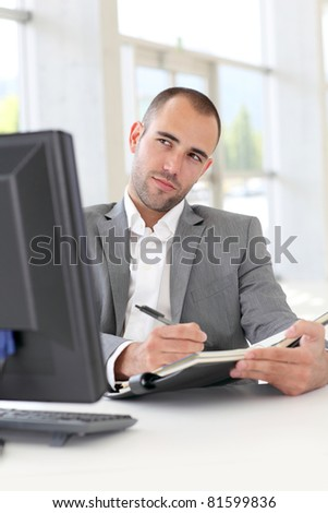 Businessman in office writing on agenda