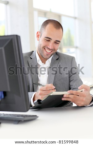 Businessman in office writing on agenda - stock photo