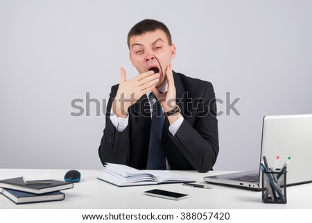 Businessman in office yawning over gray background - stock photo