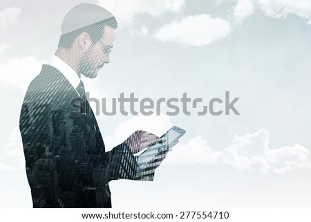 Businessman in reading glasses using his tablet pc against low angle view of skyscrapers - stock photo