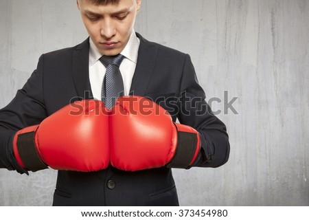 Businessman in red boxing gloves on background
