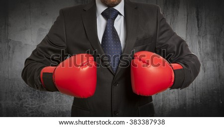 Businessman in red boxing gloves on background - stock photo
