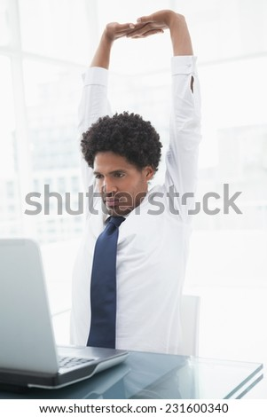 Businessman in shirt stretching his arms on the office