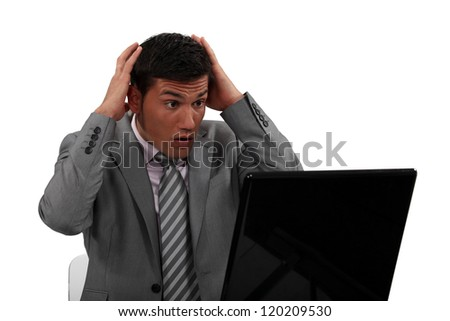 Businessman in shock at his laptop - stock photo