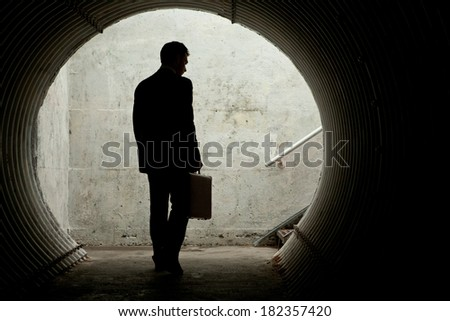 Businessman in Silhouette Walking in a dark tunnel. With room for your Text - stock photo