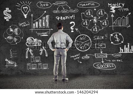 businessman in suit and business plan on grunge wall - stock photo