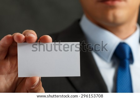 Businessman in suit and hand holding blank calling card. Male hand showing white visiting card in camera closeup. Partners contact information exchange concept. Introducing gesture at formal meeting - stock photo