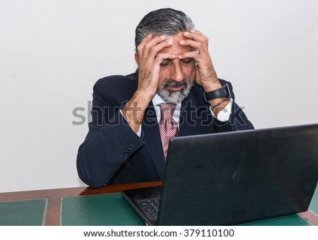 Businessman in suit and tie, desperate, in his studio. Alone in his office, in front of the desk with the computer, it panic, depression.
