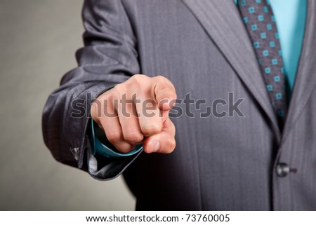 businessman in suit and tie pointing the finger in front of himself
