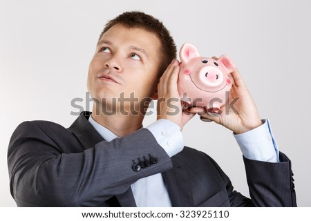 Businessman in suit and tie shaking funny piggybank and listening sound of inside detecting amount. Budgeting expenses concept. Making savings and effective investment concept. Future needs deposit - stock photo