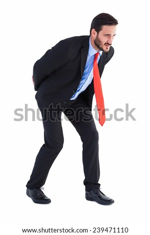 Businessman in suit carrying something heavy on white background