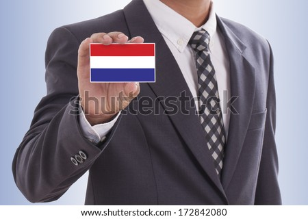 Businessman in suit hand holding a business card with Dutch Flag  - stock photo