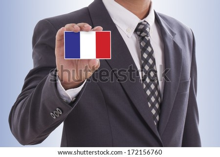Businessman in suit hand holding a business card with French Flag - stock photo