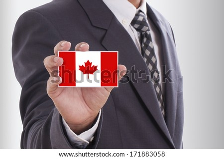 Businessman in suit holding a business card with a Canada Flag  - stock photo
