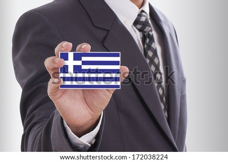 Businessman in suit holding a business card with Greek Flag