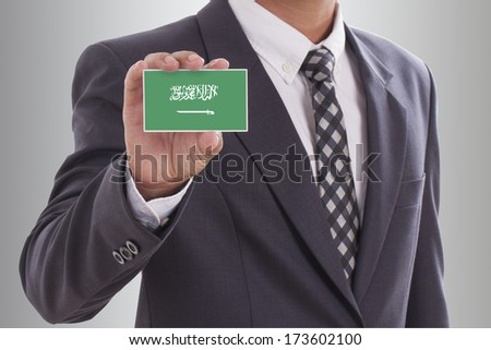 Businessman in suit holding a business card with Saudi Arabia flag  - stock photo