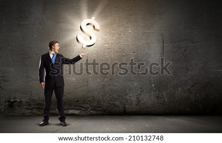Businessman in suit holding dollar sign in palm - stock photo