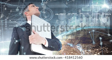 Businessman in suit holding his laptop proudly against image of a earth - stock photo