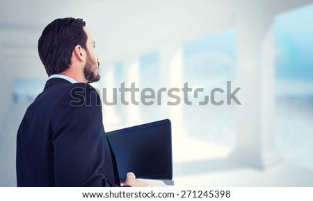 Businessman in suit holding laptop against bright white room with columns - stock photo