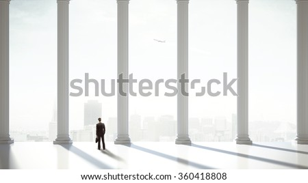 businessman in suit in the classic hall with big column - stock photo