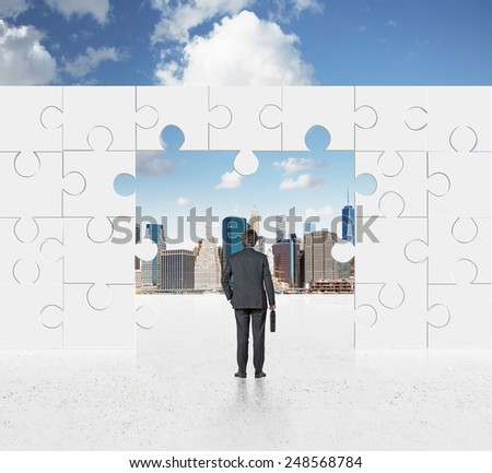 businessman in suit looking on puzzle wall