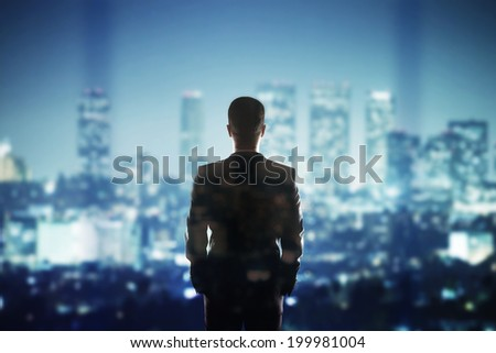 businessman in suit looking to night city - stock photo