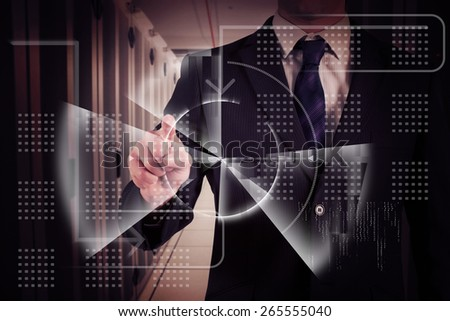 Businessman in suit pointing finger against data center - stock photo
