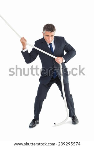 Businessman in suit pulling a rope on white background - stock photo