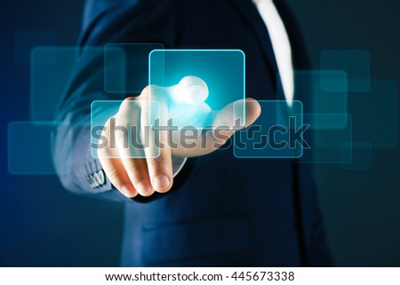 Businessman in suit pushing a button on virtual screen