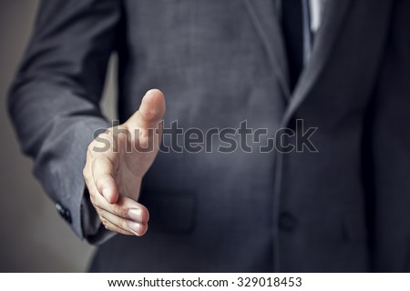 Businessman in suit ready to handshake with trust and professionalism (focus on hand, blur out the suit). It indicates many aspects such as business,finance, friendship, partnership, togetherness.