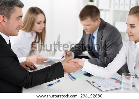 Businessman in suit shaking woman's hand with their colleagues acting at background. Partners made deal and sealed it with handclasp. Formal greeting gesture - stock photo