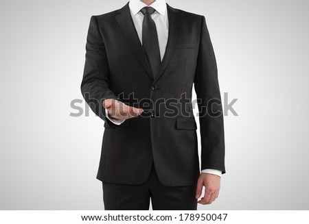 businessman in suit showing something on a gray background