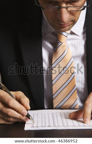 Businessman in suit sitting at desk in office working on a chart - stock photo