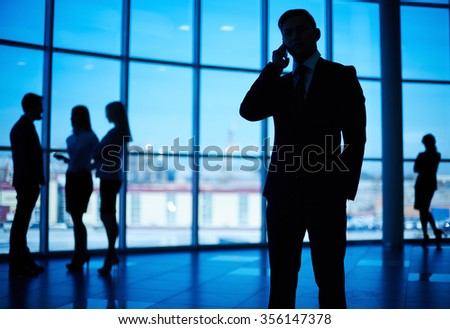 Businessman in suit speaking on the phone in modern office - stock photo