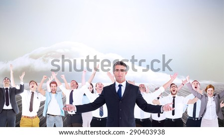 Businessman in suit spreading his arms against clouds on the horizon - stock photo