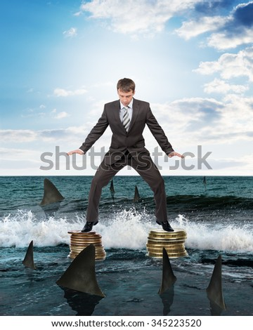 Businessman in suit standing above sharks in water