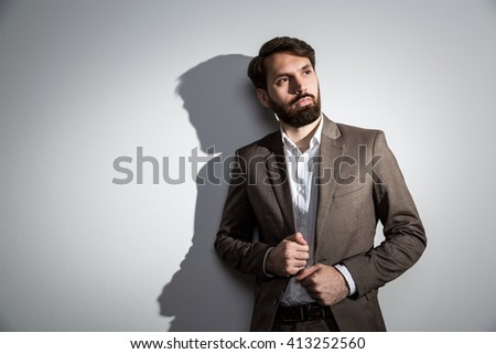 Businessman in suit standing against grey wall with shadow