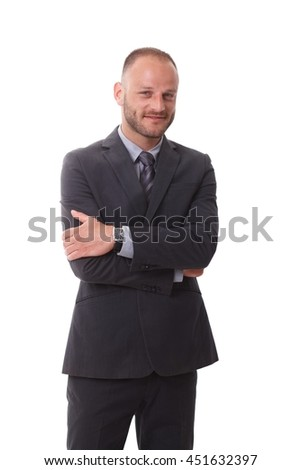 Businessman in suit standing arms crossed, smiling, looking at camera.