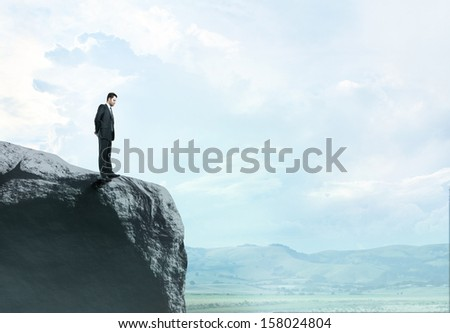 businessman in suit standing at big rock - stock photo